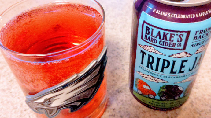 Blake's Hard Cider Triple Jam - Strawberry, Raspberry, Blackberry flavored cider - red cider in a Philadelphia Eagles Rocks Glass next to the can