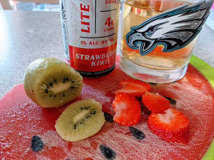 Blake's Strawberry Kiwi Lite Hard Cider Sangria Next to Cut Strawberries and Kiwis on a Cutting Board with the Cider in a Philadelphia Eagles Rocks Glass