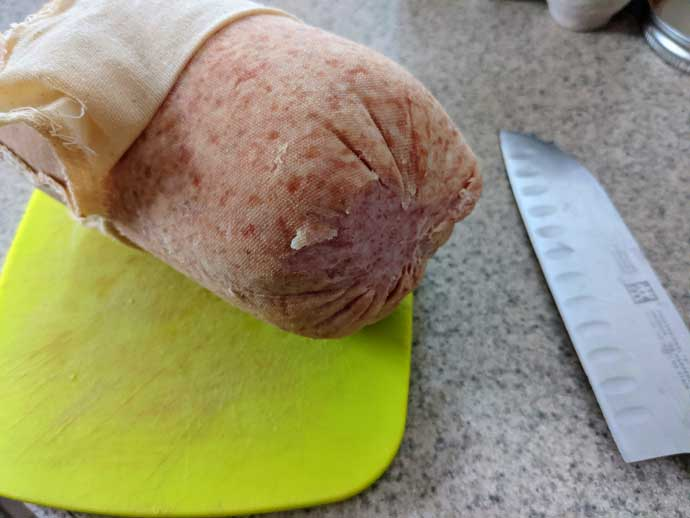 Buy in Bulk - Case Pork Roll Wrapped in Cheesecloth on a Cutting Board with a Knife
